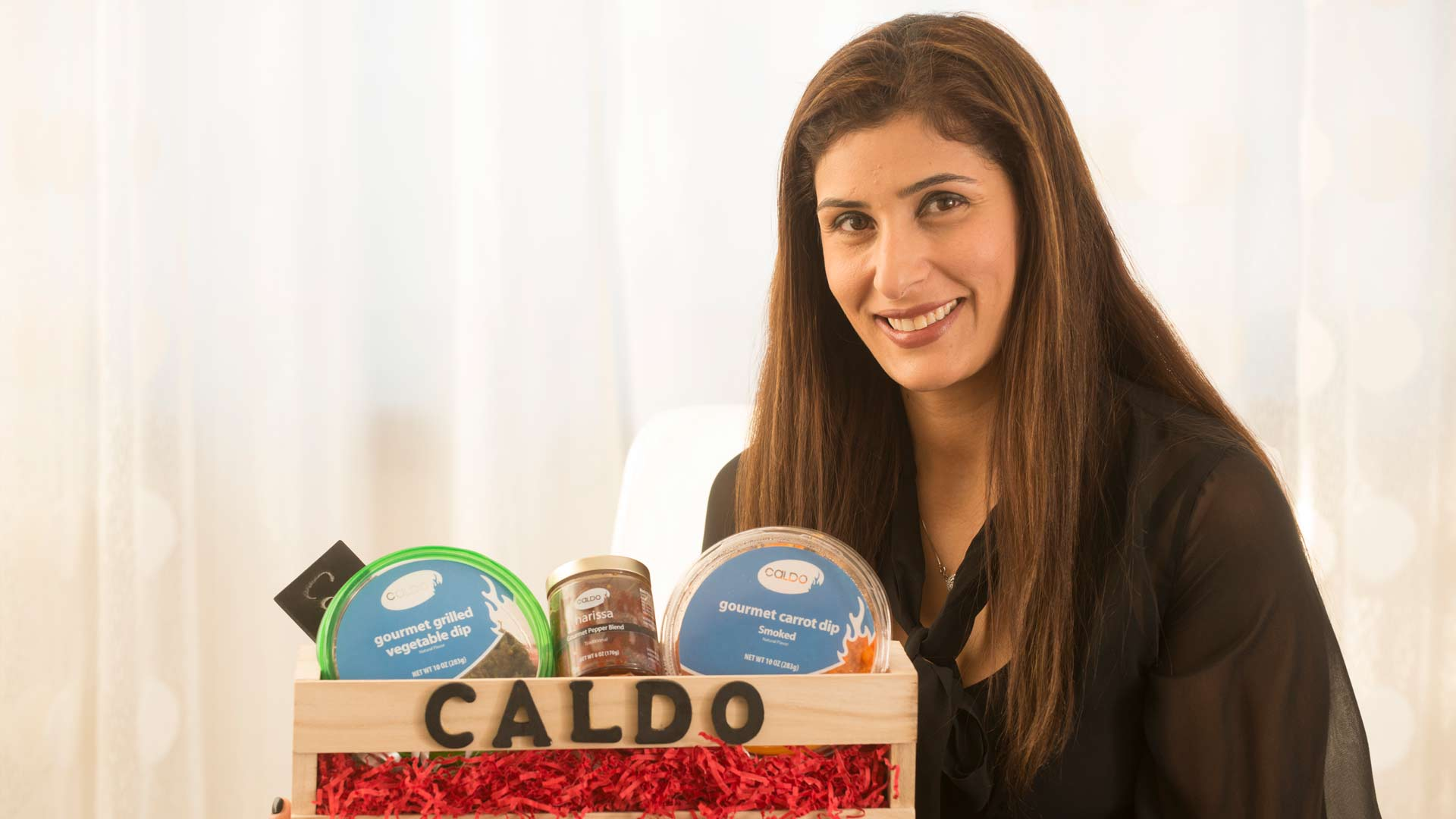 woman holding various food products from Caldo foods